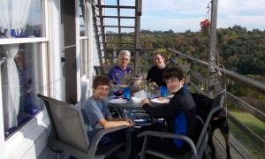 grandma and grandchildren dine on the deck